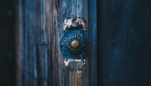 Старинный дверной металлический звонок на синей деревянной двери